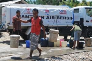 Seorang penduduk baru mengambil air bersih yang disalurkan oleh PMI cabang Solo, hasil kegiatan CSR BRI. Gambar diambil dari sini.